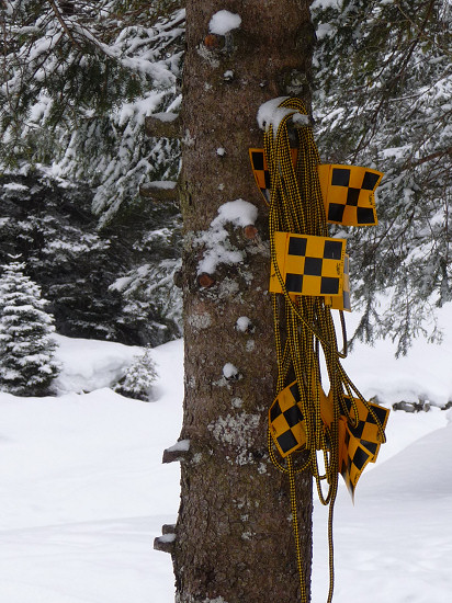 Yellow-black flags on a rope to rope of the way at avalanche risk